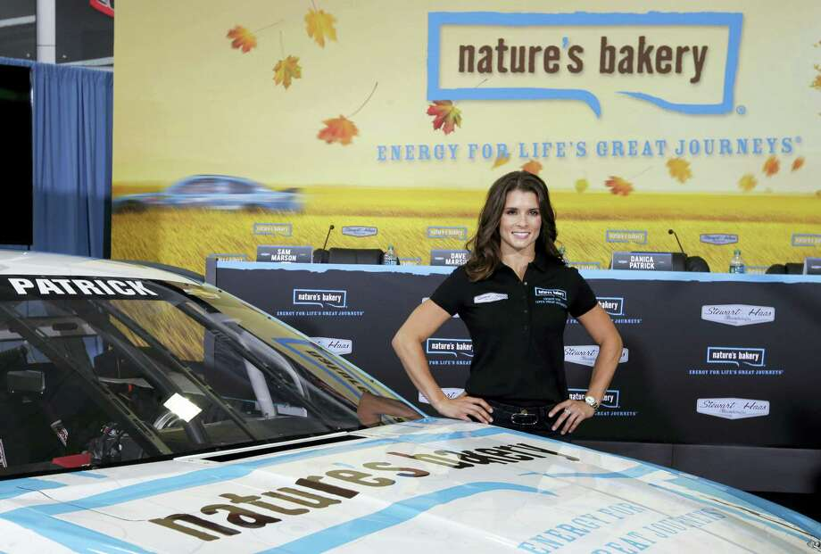 Danica Patrick poses by her new race car during a news conference. Photo: The Associated Press File Photo   / AP