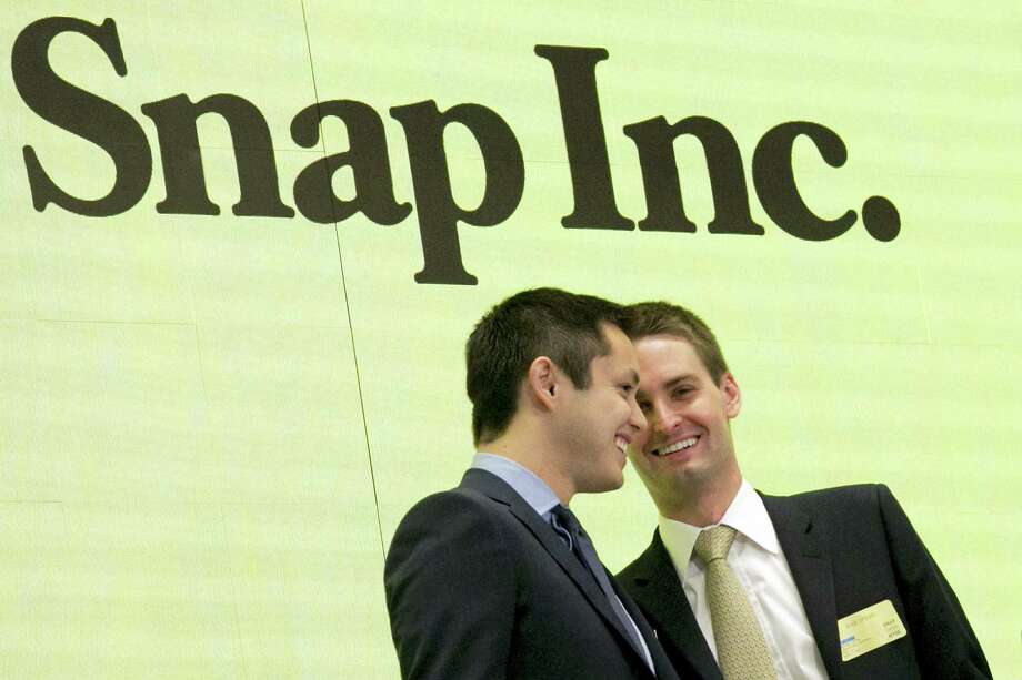 Snapchat co-founders Bobby Murphy, left, and CEO Evan Spiegel ring the opening bell at the New York Stock Exchange on March 2, 2017 as the company celebrates its IPO. Since it couldn'Äôt buy its smaller rival, Facebook is bent on copying Snap to death. Snap Inc., the company behind Snapchat, meanwhile, is intent on forging ahead against its much bigger rival, courting older users, keeping young ones and along with them, advertisers. Photo: Richard Drew — AP Photo File    / Copyright 2017 The Associated Press. All rights reserved.