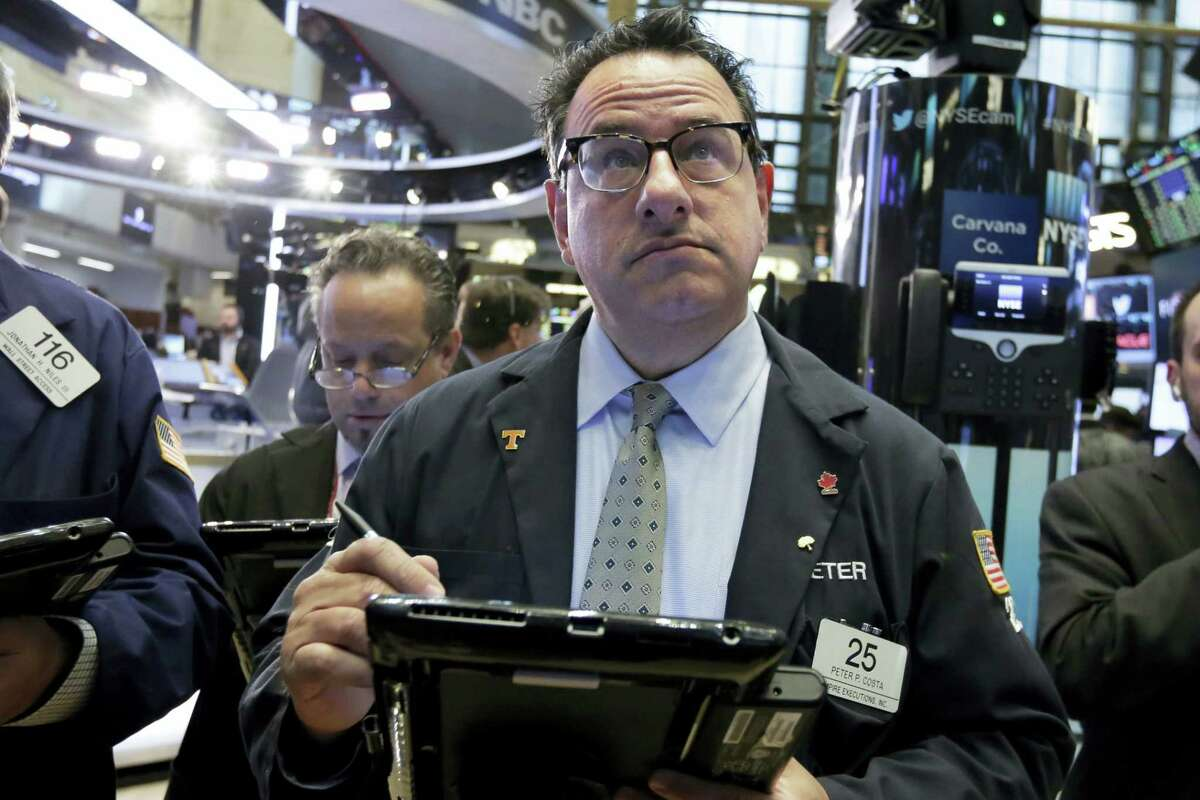 Trader Peter Costa, center, works on the floor of the New York Stock Exchange Wednesday.