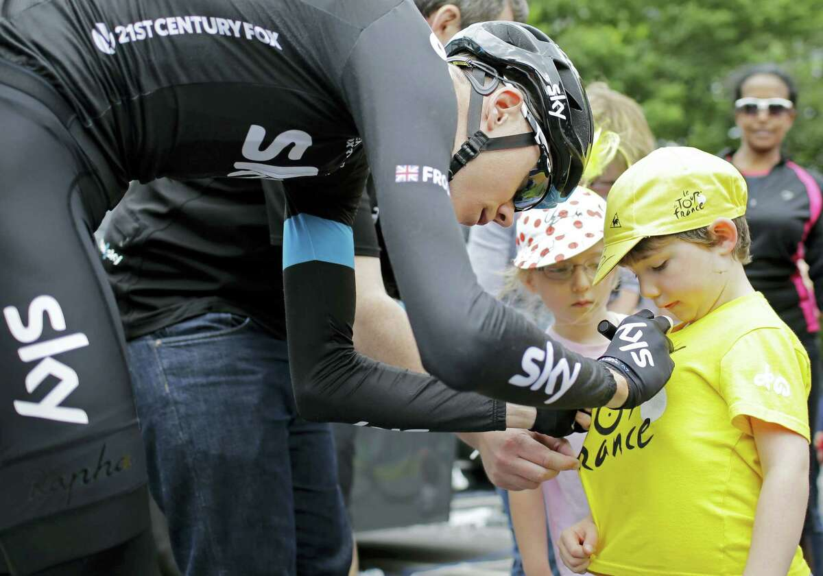Britain's Christopher Froome autographs a yellow jersey prior to leaving for a training ride ahead of the Tour de France cycling race in Leeds, Britain on July 4, 2014.