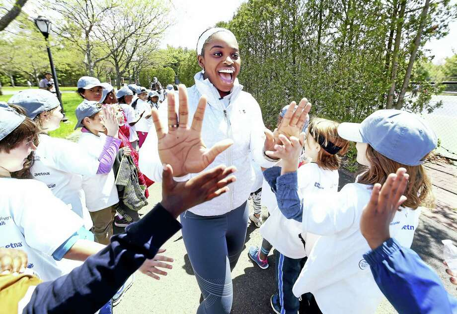 Professional tennis player Sloane Stephens (center) share high-fives with third graders from New Haven Public Schools during a free tennis clinic at the Connecticut Tennis Center courts in New Haven Tuesday. Photo: Arnold Gold — New Haven Register