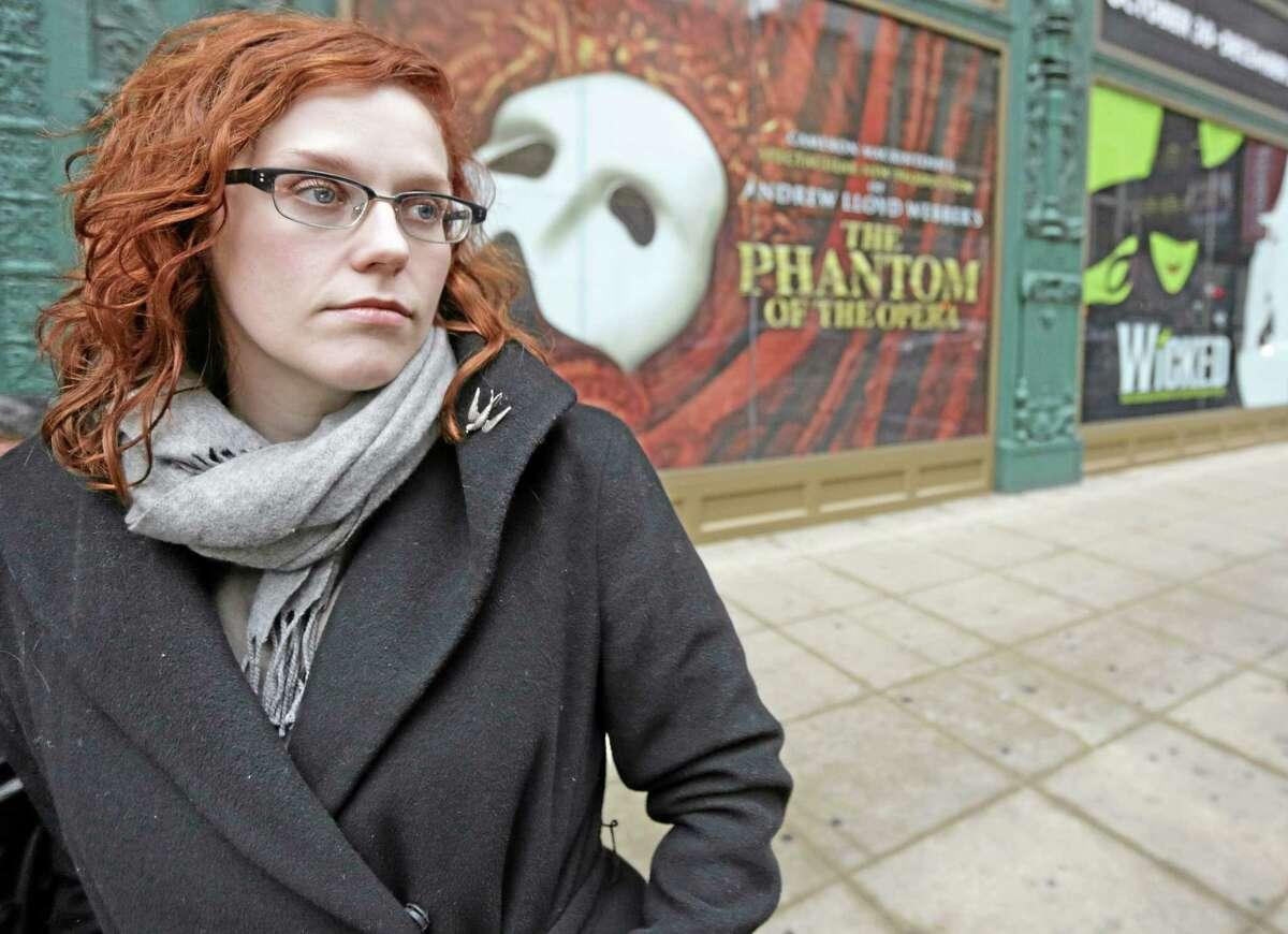 In this Dec. 3, 2013, photo, actor Adrienne Matzen poses in Chicago's theater district. Matzen, 29, who has been mostly uninsured since she turned 21, is now looking for a low monthly premium insurance plan on the federal website.