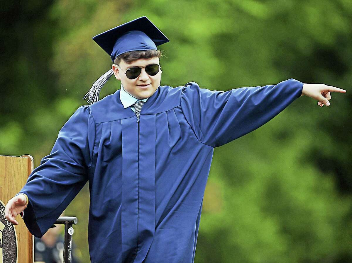 Morgan School graduate Irvin Ariel Andrade Velez points out to the crowd as his name is called to receive his diploma Tuesday in Clinton.