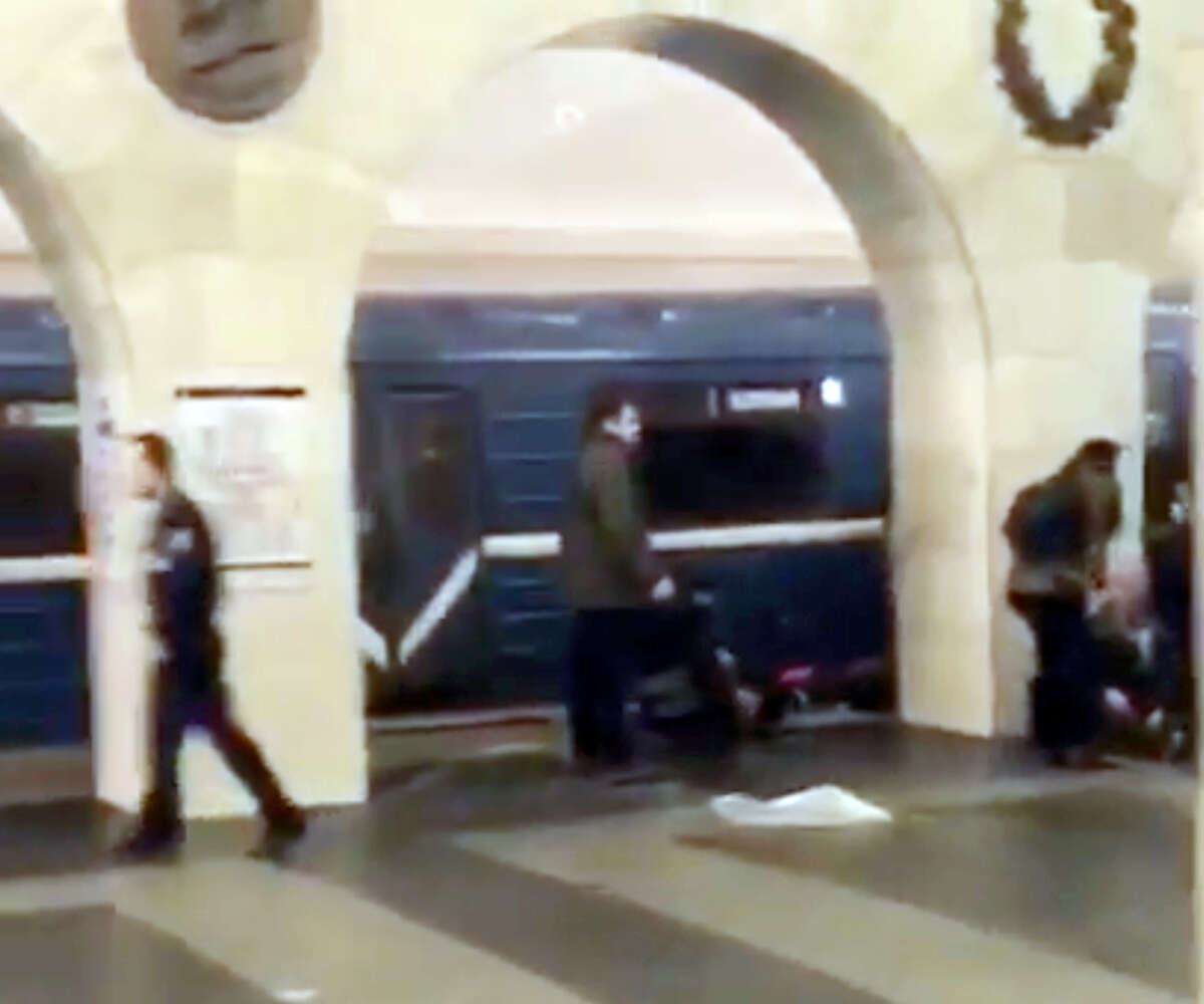 In this grab taken from AP video, Russian police officer, left, and people walk past the damaged train at the Tekhnologichesky Institut subway station in St.Petersburg, Russia on Monday, April 3, 2017. The subway in the Russian city of St. Petersburg is reporting that several people have been injured in an explosion on a subway train. (AP video via AP)