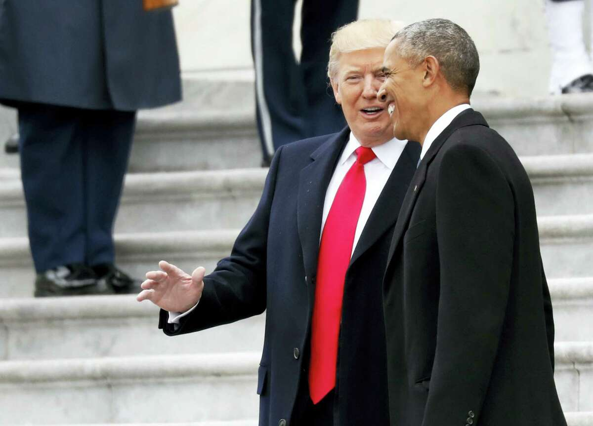 President Donald Trump and former President Barack Obama talk, as they pause on the steps of the East Front of the U.S. Capitol as the Obama's depart, Friday in Washington.