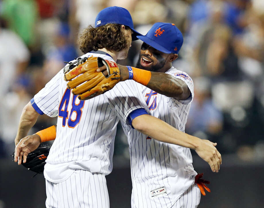 Mets third baseman Jose Reyes, right, embraces starting pitcher Jacob deGrom after deGrom pitched a complete game in the Mets 6-1 win over the Cubs on Monday. Photo: Kathy Willens — The Associated Press   / Copyright 2017 The Associated Press. All rights reserved.