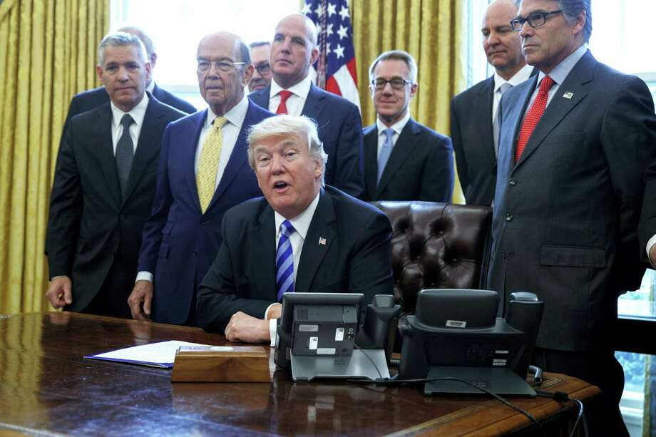 In this March 24, 2017 photo, President Donald Trump announces the approval of a permit to build the Keystone XL pipeline, clearing the way for the $8 billion project in the Oval Office of the White House in Washington. From left are, TransCanada CEO Russell K. Girling, Commerce Secretary Wilbur Ross and Energy Secretary Rick Perry. Amid staff turmoil and shake-ups, travel bans blocked by federal courts and the Russia cloud hanging overhead, Trump is plucking away at another piece of his agenda: undoing Obama. Photo: AP Photo — Evan Vucci   / Copyright 2017 The Associated Press. All rights reserved.