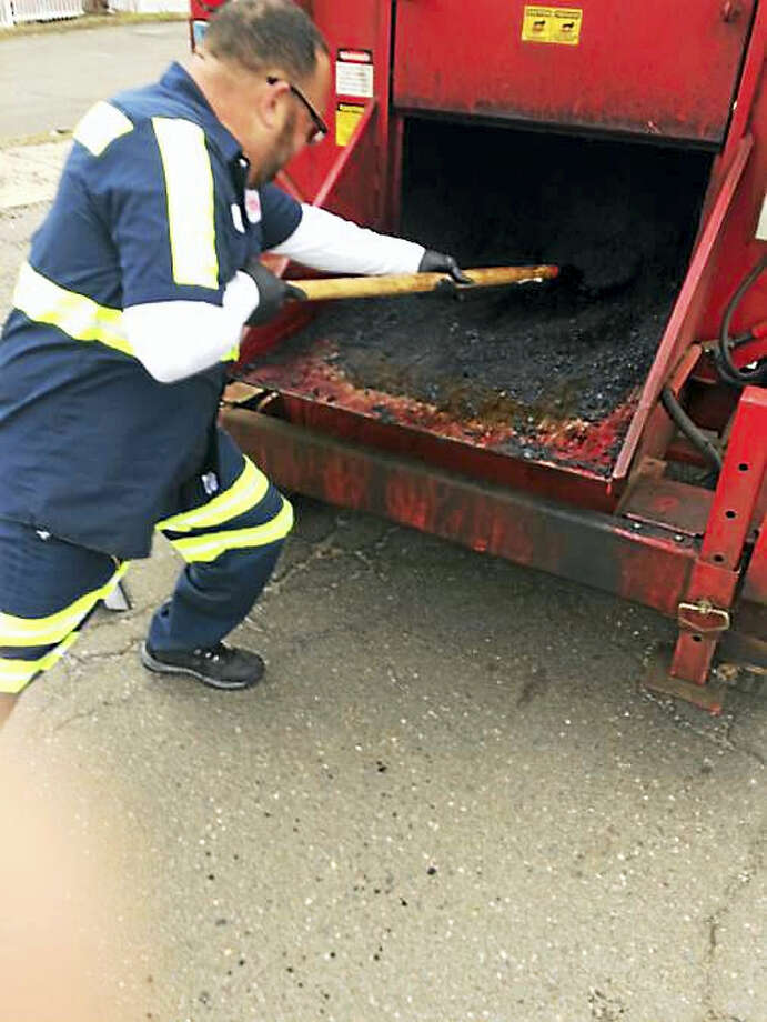 New Haven Department of Public Works employees Domingo Rivera and Julio Perez fill in potholes on Flint Street. Photo: WILLIAM KAEMPFFER — NEW HAVEN REGISTER