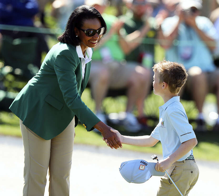 Carter Kontur, right, shakes hands with former Secretary of State Condoleezza Rice after putting on the 18th green during the Drive Chip & Putt finals at Augusta National on Sunday. Photo: Curtis Compton — Atlanta Journal-Constitution Via AP   / Atlanta Journal-Constitution