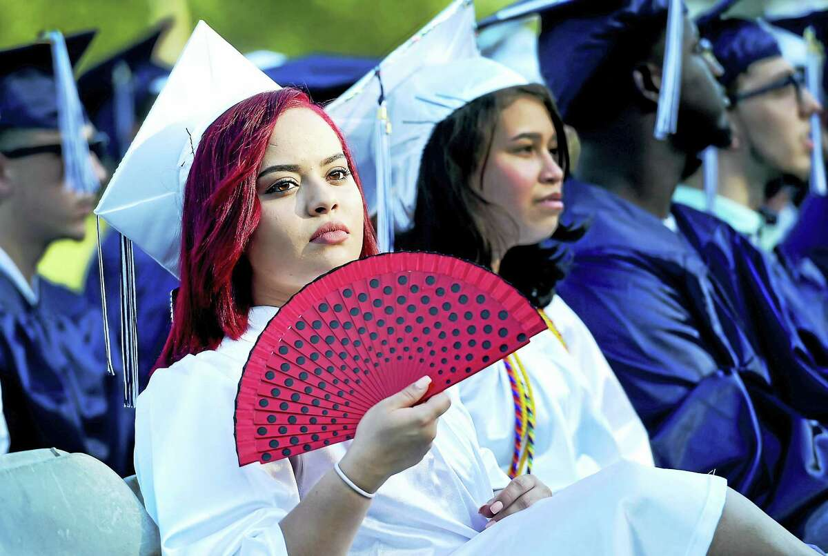 Aryanna Yveliz Torres keeps herself cool during Ansonia High School commencement exercises at Jarvis Field in Ansonia Monday evening.