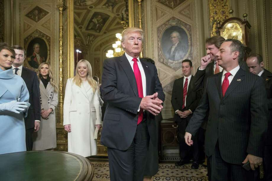 President Donald Trump leaves the President's Room of the Senate on Capitol Hill in Washington on Friday after he formally signed his cabinet nominations into law. He is joined at far left by his wife, first lady Melania Trump and daughter Tiffany Trump. At far right is Chief of Staff Reince Priebus, with White House counsel Donald McGahn, second from right. Photo: J. Scott Applewhite — AP Pool Photo / AP
