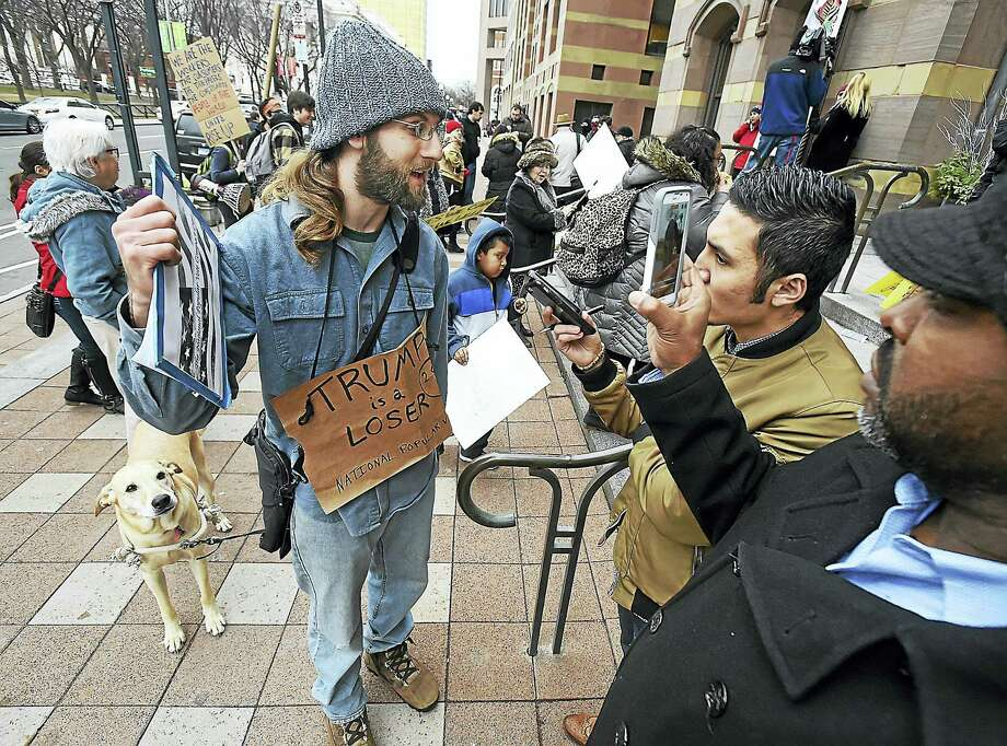 Steven Winter of New Haven, left, a member of the National Popular Vote Compact CT, talks to New Haven Register reporters Esteban L. Hernandez and Shahid Abdul-Karim while collecting signatures to abolish the Electoral College during an anti-Trump protest Friday at New Haven City Hall. Photo: Catherine Avalone — New Haven Register   / Catherine Avalone/New Haven Register