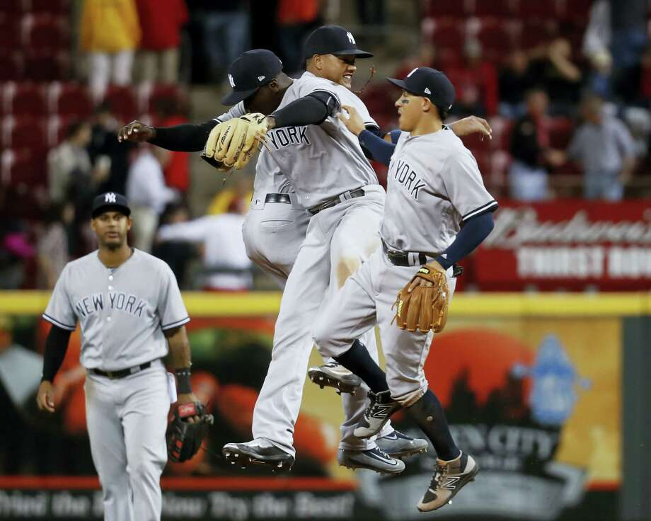 Members of the Yankees celebrate after beating the Reds on Monday night. Photo: John Minchillo — The Associated Press   / AP