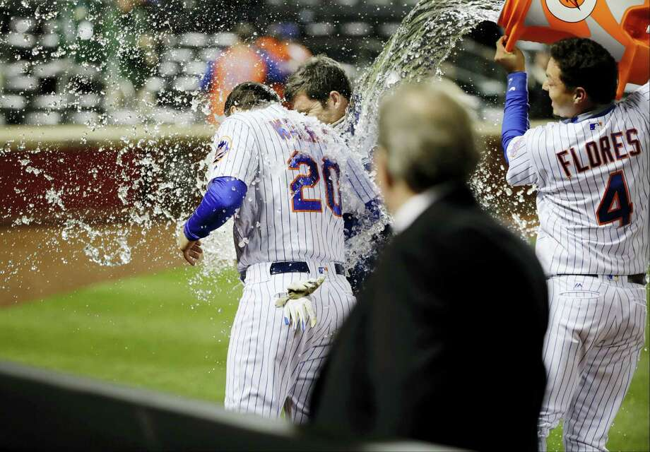 The Mets' Wilmer Flores (4) dumps a cooler on Neil Walker after Monday's win. Photo: Frank Franklin II — The Associated Press   / Copyright 2017 The Associated Press. All rights reserved.