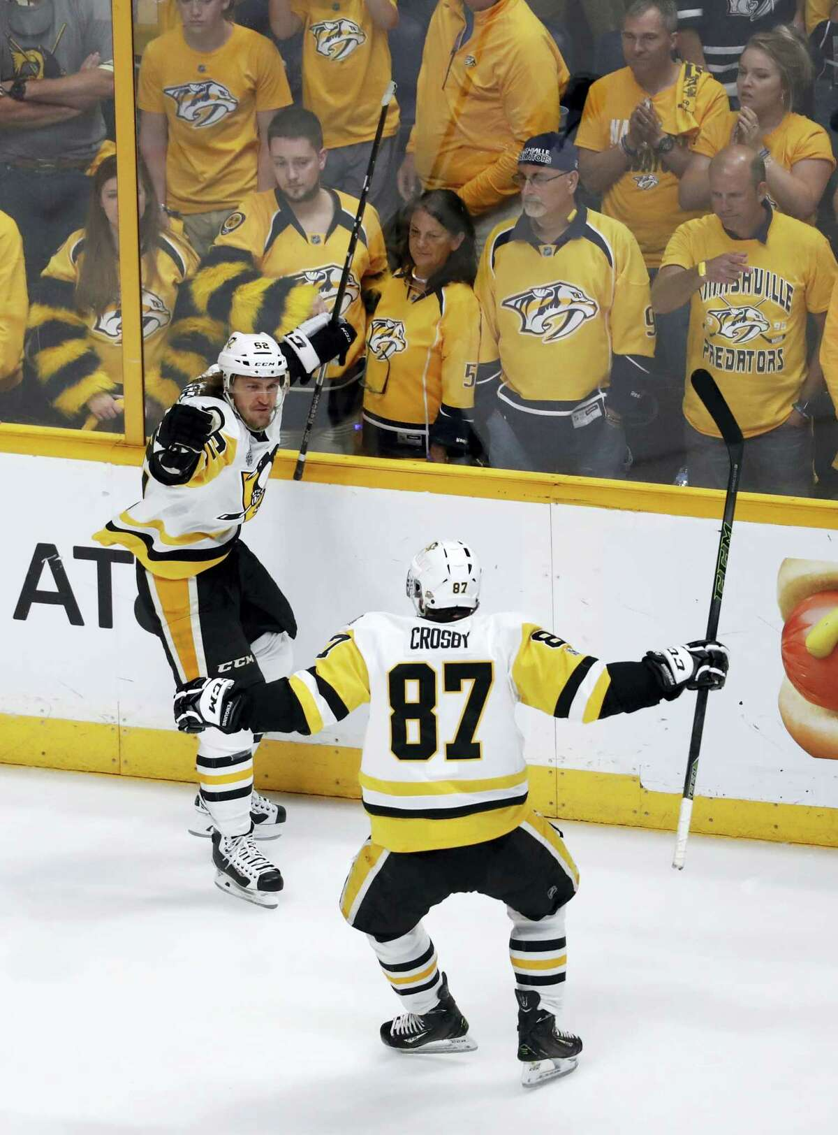 Pittsburgh Penguins' Carl Hagelin (62), of Sweden, celebrates with Sidney Crosby (87) after scoring a goal against the Nashville Predators during the third period of Game 6 of the NHL hockey Stanley Cup Final, Sunday in Nashville, Tenn.