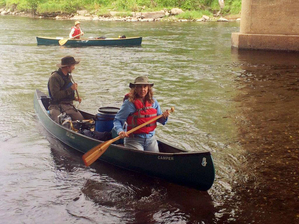 """In this June 4, 2017 photo, Paddlers Lisa Dahill and Mark Kutolowski in the front canoe and Steve Blackmer in the back paddle in to a campsite along the Connecticut River in North Stratford, N.H. Episcopal dioceses in New England have organized a 40-day """"River of Life"""" pilgrimage of canoeists and kayakers of all faiths along the 400-mile river, trading cellphones for paddles to partake in a spiritual journey."""