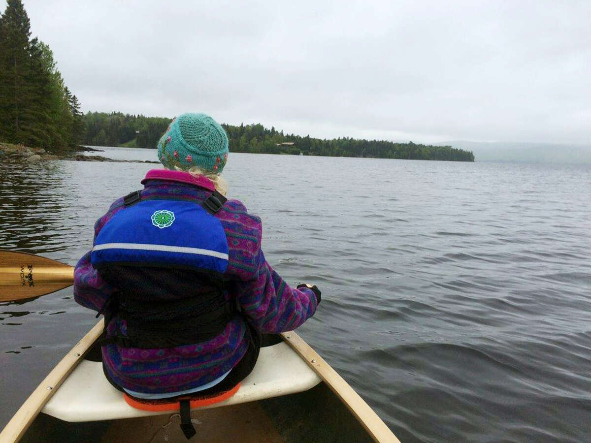 """In this June 3, 2017, Elizabeth Stevens paddles along the western edge of the First Connecticut Lake near the headwaters of the Connecticut River, northeast of Pittsburg, N.H. Episcopal dioceses in New England have organized a 40-day """"River of Life"""" pilgrimage of canoeists and kayakers of all faiths along the 400-mile river, trading cellphones for paddles to partake in a spiritual journey."""