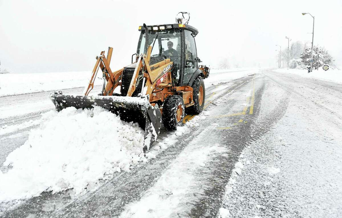 In this file photo from Feb. 2016, Robert Maselli of the West Haven Public Works Department clears snow from Captain Thomas Blvd. in West Haven.