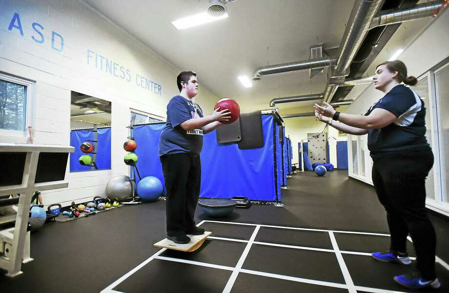 Standing on a balance board, Nick Keating, 16, passes a medicine ball to head trainer, Jackie Sanca, during a 30 minute personal training session at the Autism Spectrum Disorder Fitness Center at 307 Racebrook Road in Orange. Photo: Catherine Avalone - New Haven Register   / Catherine Avalone/New Haven Register