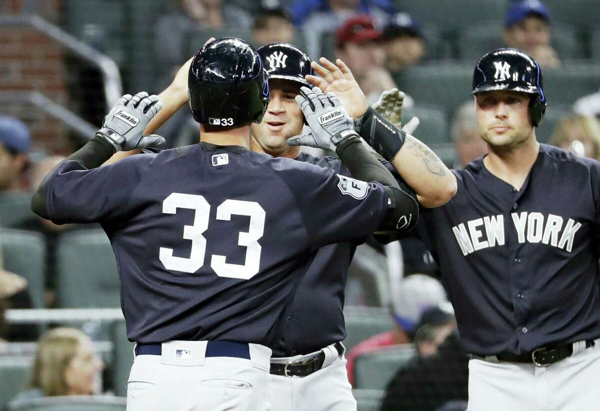 The Yankees' Greg Bird (33) is high-fived by teammate Gary Sanchez after they scored on a home by Bird in a spring training game.