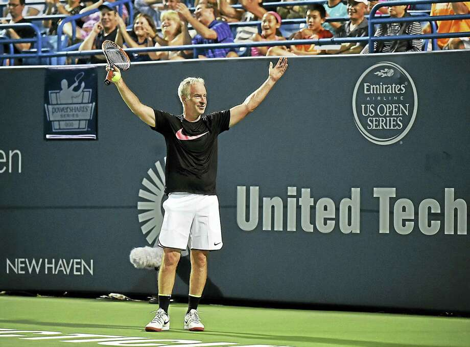 After seeing the replay, John McEnroe celebrates during the Men's Legends match after challenging a call against James Blake last year. McEnroe and Blake will return again this August to the event. Photo: CATHERINE AVALONE — NEW HAVEN REGISTER   / New Haven RegisterThe Middletown Press