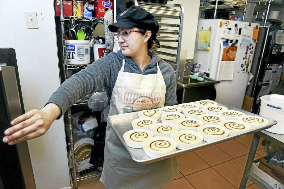 Sonia Aprea, owner of Sweet Treats by Sonia, puts a tray of caramel pecan stickies into the oven in the kitchen of Moon Rocks Gourmet Cookies in Hamden. Photo: Arnold Gold — New Haven Register