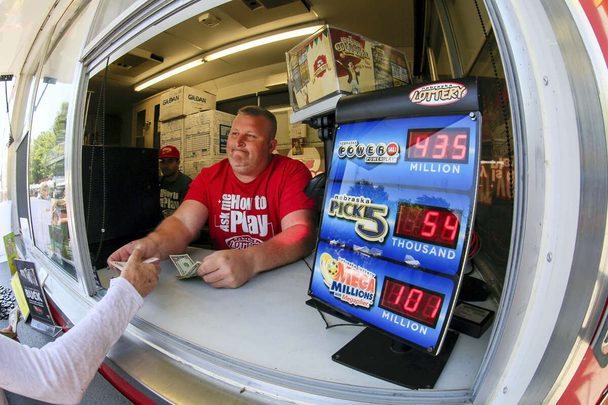 Chris Raff of Lincoln, Neb., hands a Powerball ticket to a customer in Omaha, Neb. on June 10, 2017. The Powerball lottery jackpot has grown to an estimated $435 million, after more than two months without a winner.