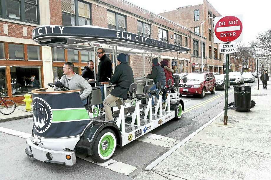 Elm City Party Bike co-owner Christian Bruckhart at the wheel of the party and sightseeing bike waits for the light to change at the corner of High and Chapel Street in New Haven on 4/1/2017.  Standing behind him is co-owner Colin Caplan. Photo: Arnold Gold-New Haven Register