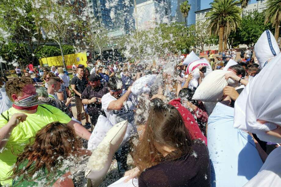 Feathers fly as participants take part in a giant pillow fight in Pershing Square in downtown Los Angeles on Saturday, April 1, 2017. Hundreds of people traded soft blows in in a giant pillow fight that dwarfed even the biggest slumber party slugfests. Children, teens, adults and seniors swung pillows at one another for over an hour on Saturday. The annual event is held to celebrate International Pillow Fight Day. Photo: AP Photo/Richard Vogel / Copyright 2017 The Associated Press. All rights reserved.