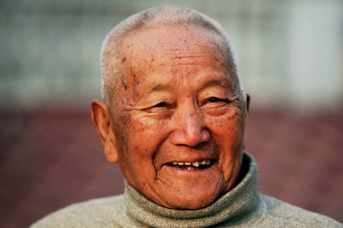 In this April 12, 2017 photo, Nepalese mountain climber Min Bahadur Sherchan, 85, smiles as he finishes his morning yoga workout at his residence in Kathmandu, Nepal. Officials say Sherchan who was attempting to scale Mount Everest to regain his title as the oldest person to scale the world's highest peak has died at the base camp on Saturday, May 6, but were not clear about the cause of the death.