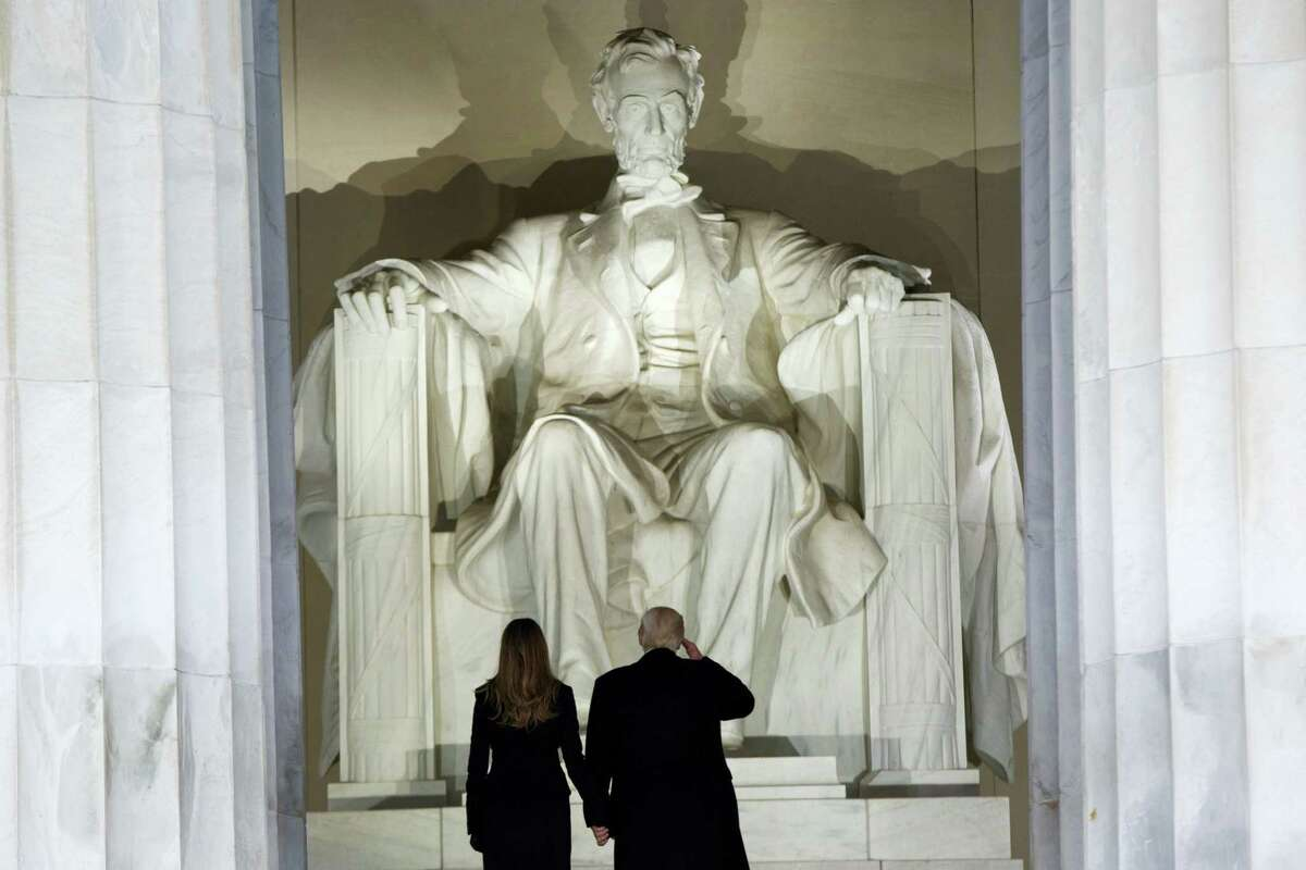 """President-elect Donald Trump, right, salutes as he arrives with his wife Melania Trump to the """"Make America Great Again Welcome Concert"""" at the Lincoln Memorial, Thursday, Jan. 19, 2017, in Washington."""