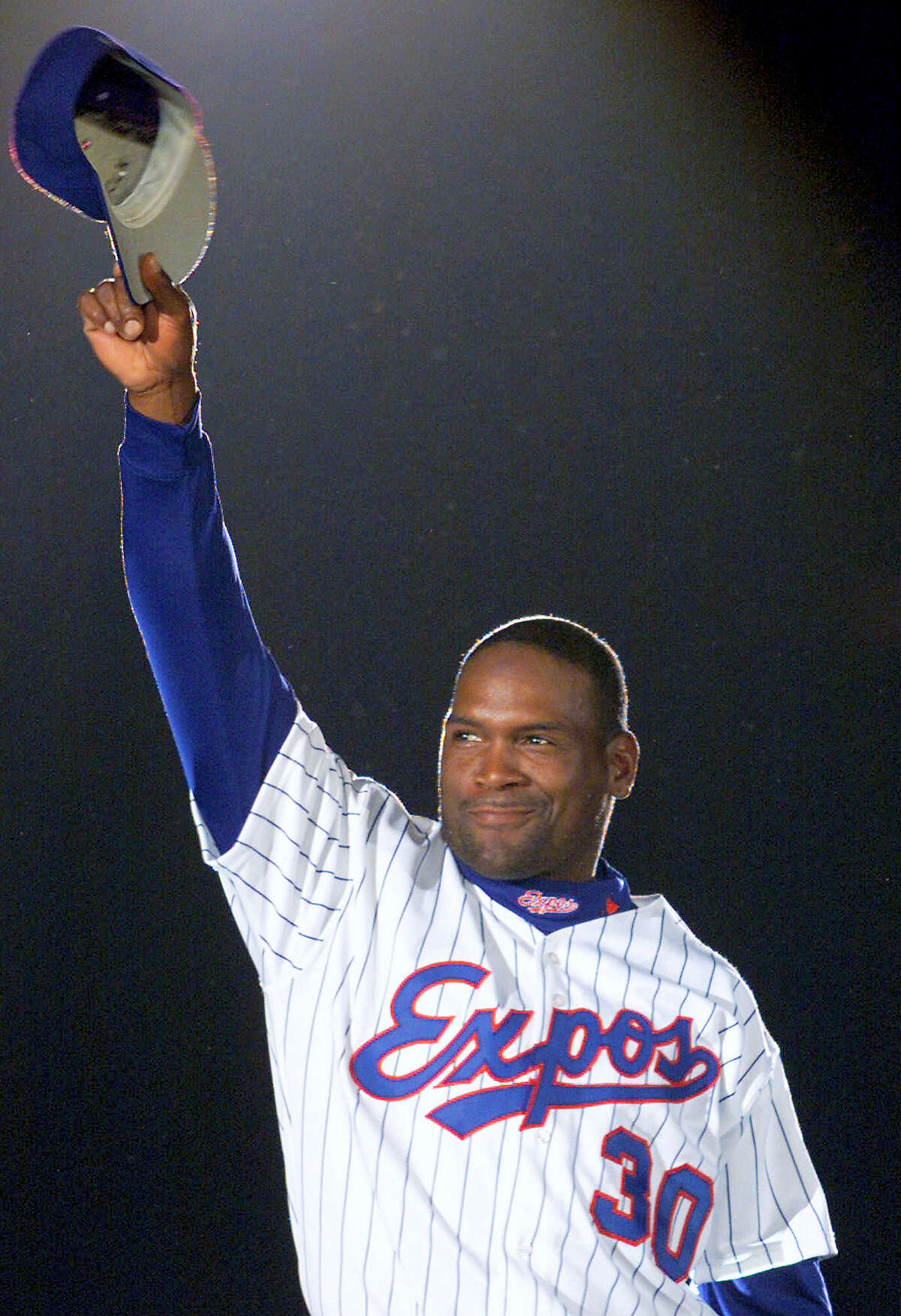Montreal Expos' Tim Raines acknowledges applause from fans as he is presented before the Expos home opener in Montreal in 2001.