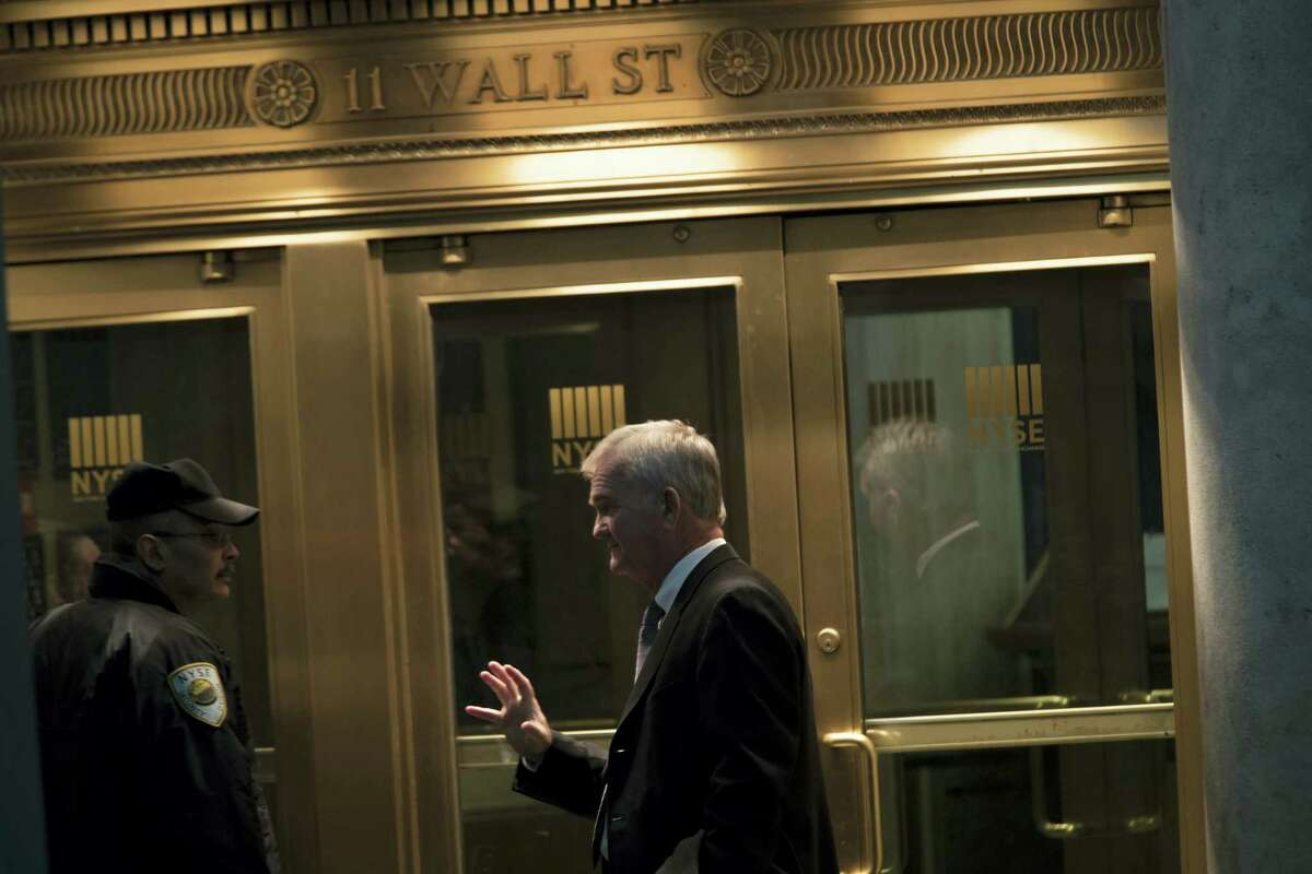A trader speaks to a security guard as he leaves the New York Stock Exchange in lower Manhattan.
