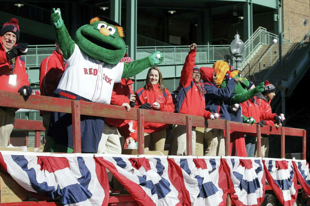 Red Sox mascot Wally the Green Monster, second from left, rides on the back of a truck with team ambassadors as part of festivities to see off the team's equipment truck at Fenway Park on Monday.
