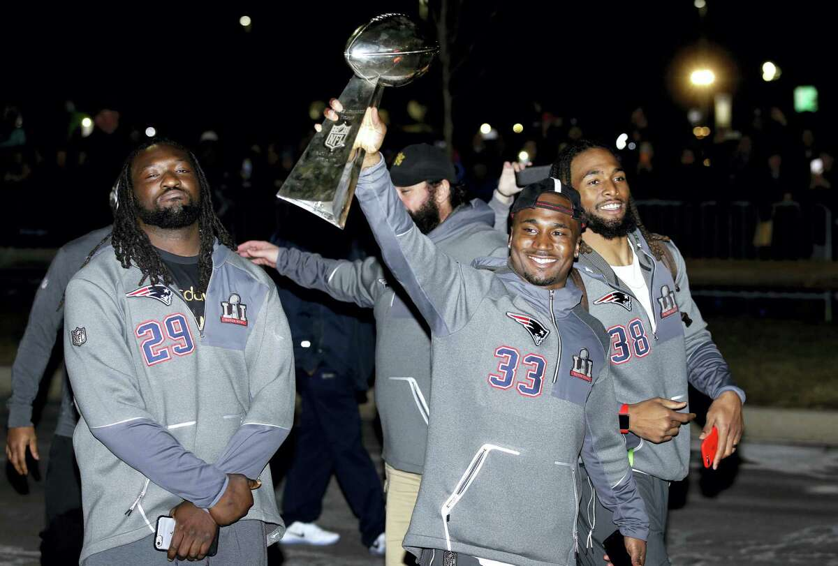 Members of the Patriots, from left, LeGarrette Blount, Dion Lewis, and Brandon Bolden, walk with the Super Bowl trophy as they greet fans outside Gillette Stadium Monday in Foxborough, Mass.