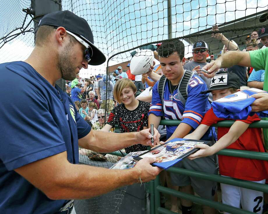Tim Tebow accommodates some lucky fans with an autograph before a minor league game in Hickory, N.C. Photo: Ernie Masche — The Hickory Daily Record Via AP   / The Hickory Daily Record