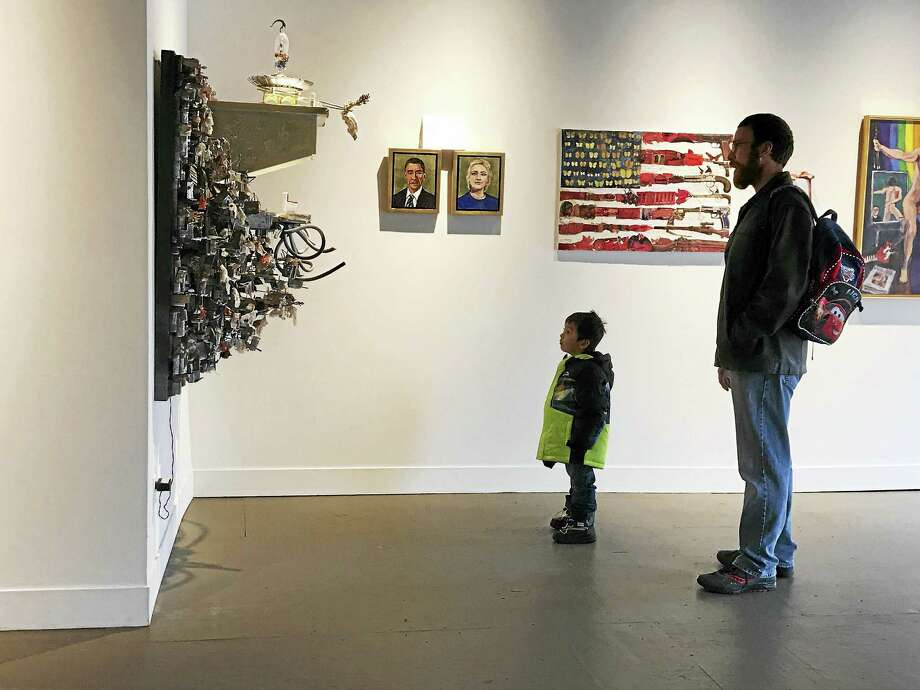 """Patrons view at three-dimensional piece called """"His Majesty's Throne"""" by Mohamad Hafez, multimedia; along with (on back wall) """"Obama"""" and """"Hilary"""" by Jonathan Weinberg, acrylic on panel; and """"American Pulse"""" by Hilary Opperman, encaustic mixed media. Photo: Toni-Ann Giammona Photo"""