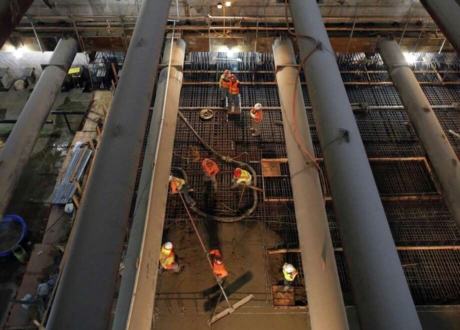 Workers more than 100 feet below ground are seen through trusses as they pour concrete to create the Union Square Sta tion platform of the Central Subway, which faces a long delay. Photo: Michael Macor / Michael Macor / The Chronicle / ONLINE_YES