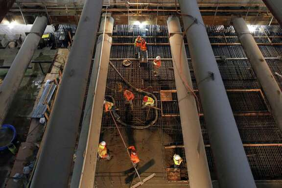 Workers more than 100 feet below ground are seen through trusses as they pour concrete to create the Union Square Sta tion platform of the Central Subway, which faces a long delay.