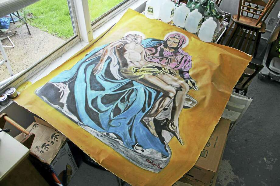 Ralph Milione's colorful painting of Pieta stretched out atop a dining table in his home in New Haven in April. Photo: Esteban L. Hernandez — New Haven Register