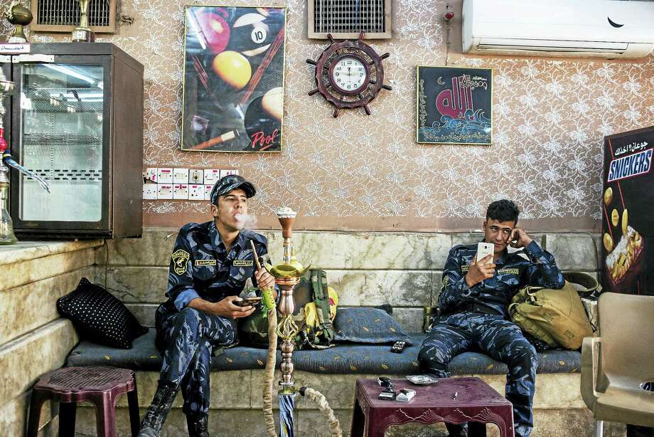 Iraqi Federal Police members take a break at the Captain pool hall in Mosul, Iraq, one smoking a water pipe and both checking their cellphones. Photo: Alex Potter  — The Washington Post    / Alex Kay Potter for The Washington Post.