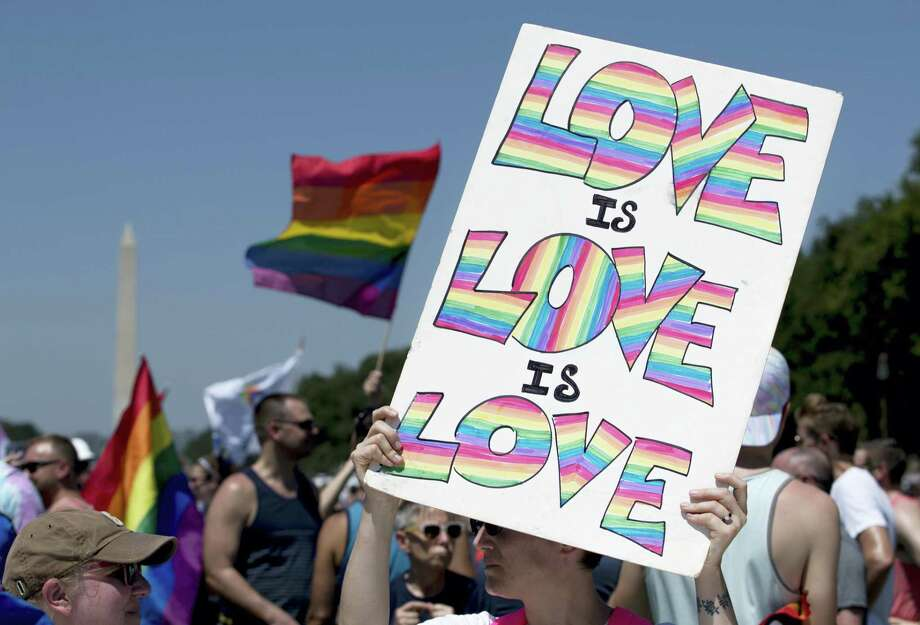 """A marcher hold a sign that reads """"Love is Love is Love"""" on the National Mall with the Washington Monument in the background during the Equality March for Unity and Pride in Washington, Sunday, June 11, 2017. (AP Photo/Carolyn Kaster) Photo: AP / Copyright 2017 The Associated Press. All rights reserved."""