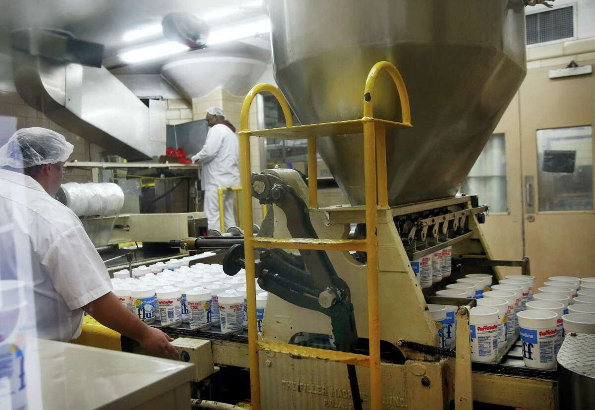 In this Sept. 27, 2013 photo, containers are filled with Marshmallow Fluff and move along an assembly line during production in Lynn, Mass. Archibald Query invented Fluff in 1917 in the Boston suburb of Somerville. The marshmallow concoction that's been smeared on a century's worth of sandwiches has inspired a festival and other sticky remembrances as it turns 100 in 2017.