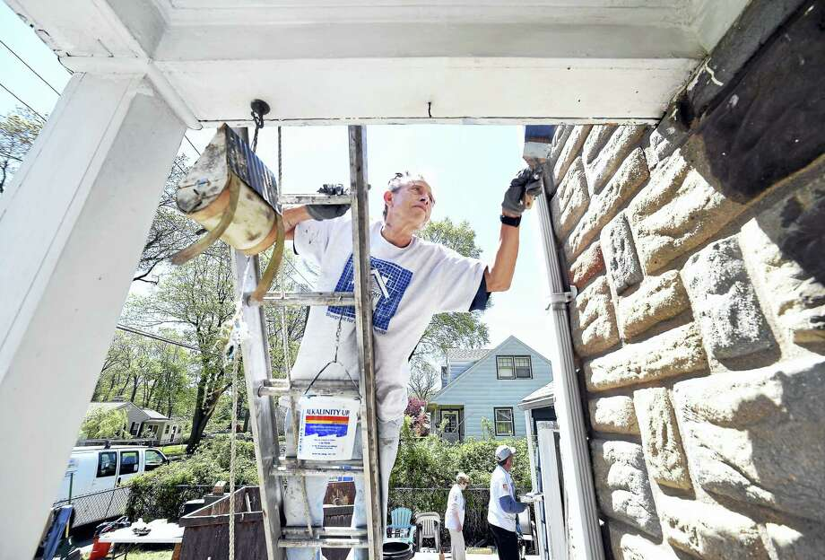 Larry Romer of Milford paints the front porch area of Nancy Palmer's home in Milford. This is one of sixty homes in New Haven County that are being revitalized for low-income families during the 30th annual HomeFront Day. Members of St. Ann Church and St. Gabriel Church volunteered for work at this home. Photo: Arnold Gold — New Haven Register