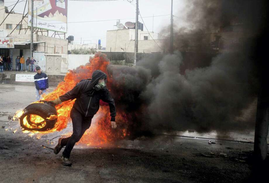 A Palestinian throws a burning tire during clashes with Israeli troops at Qalandia checkpoint near the West Bank city of Ramallah, Friday Oct. 31, 2014. Israel reopened a contested Jerusalem holy site, known to Jews as the Temple Mount and Muslims as the Noble Sanctuary, on Friday and deployed more than 1,000 security personnel following clashes the previous day between Palestinians and Israeli riot police that had ratcheted up already heightened tensions in the city. Photo: Majdi Mohammed — AP File Photo / AP