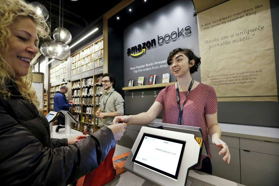 Customer Kirsty Carey, left, gets ready to swipe her credit card for clerk Marissa Pacchiarotti, as she makes one of the first purchases at the opening day for Amazon Books, the first brick-and-mortar retail store for online retail giant Amazon, in Seattle. Photo: Elaine Thompson — The Associated Press File   / Copyright 2017 The Associated Press. All rights reserved.