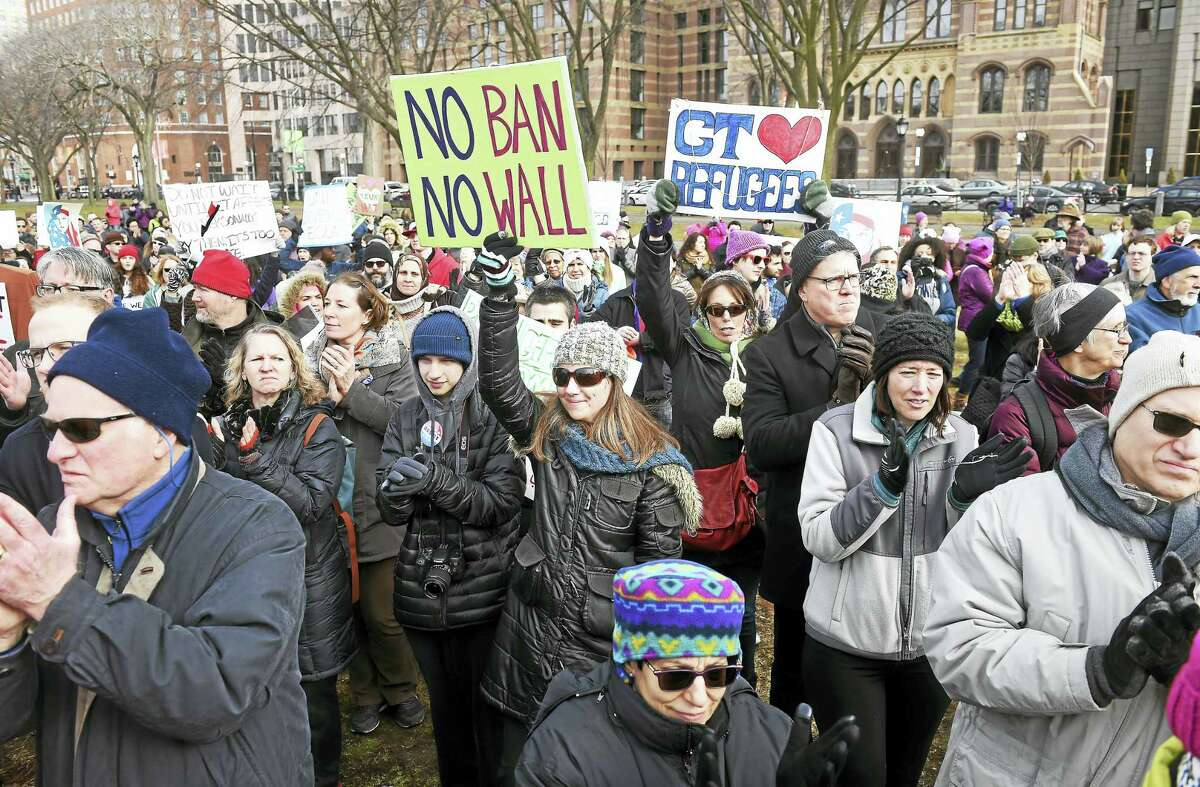 IRIS and their supporters listen to speakers on the New Haven Green at a rally following the March for Refugees Sunday in response to President Trump's executive order concerning a temporary immigration ban from seven Muslim-majority countries.