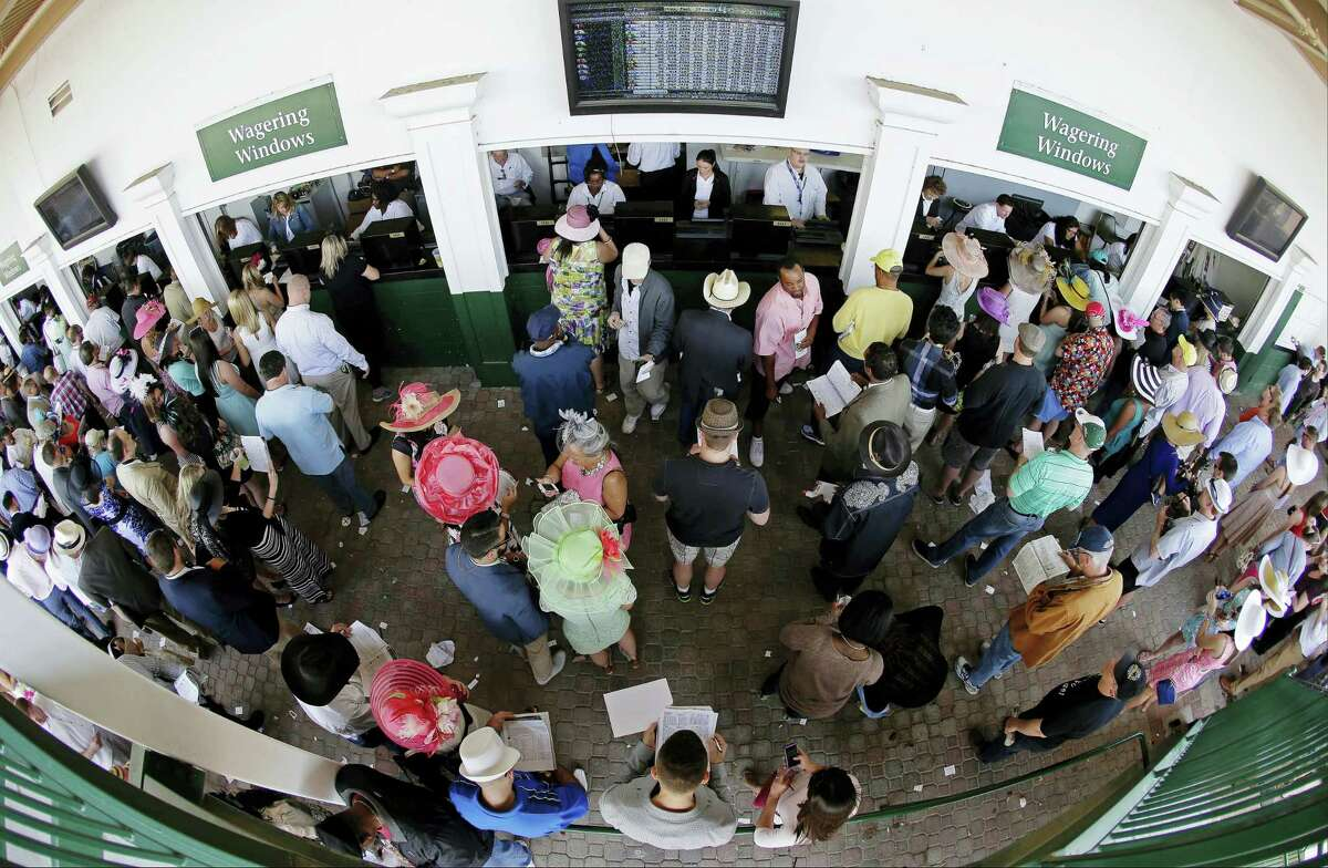 Fans line up to place bets before the 140th running of the Kentucky Derby at Churchill Downs in Louisville, Ky.