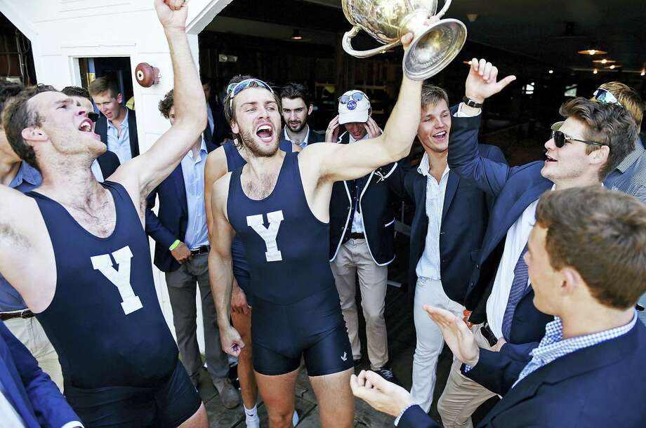 Yale bowman Ollie Wynne-Griffith hoists the Sexton Cup as the Bulldogs celebrate the heavyweight crew team's win at the annual Harvard/Yale regatta in Ledyard. Photo: Sean D. Elliot — The Day Via AP   / 2017 The Day Publishing Company