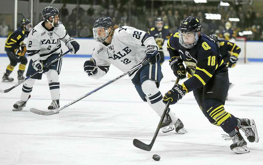 Quinnipiac's Nick Jermain skates past Yale' J.M. Piotrowski during Saturday's game at Ingalls Rink in New Haven. Photo: Catherine Avalone — Register   / Catherine Avalone/New Haven Register